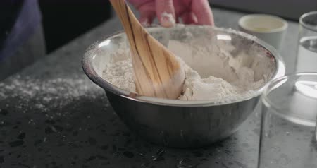 grissini : Slow motion man mixing dry ingredients with flour in steel bowl on concrete countertop