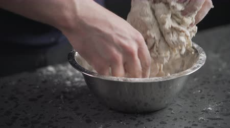 olive oil pour : man mixing dough in steel bowl on concrete countertop