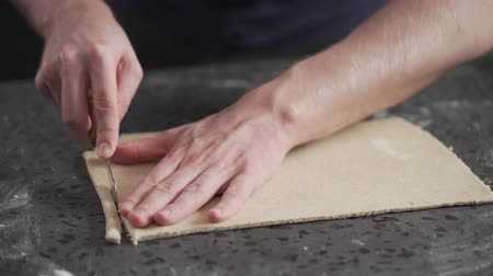 grissini : man slicing flat dough with knife for making grissini