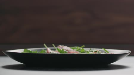 antipasti : Slow motion prosciutto falling into black plate with arugula leaves Stock Footage