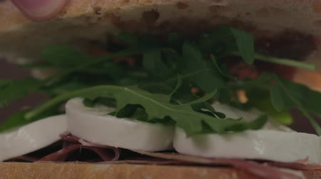incir : Slow motion man hand put top on sandwich closeup