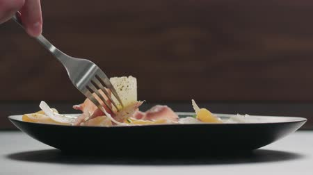 プロシュート : Slow motion man hand pick salad with arugula, prosciutto and tangerine in black plate