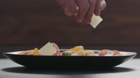 mandarini : Slow motion making salad man adding parmesan into black plate with arugula, prosciutto and tangerine Filmati Stock