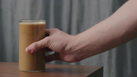 americano : Slow motion man hand take coffee with cream in glass from walnut table Stock Footage