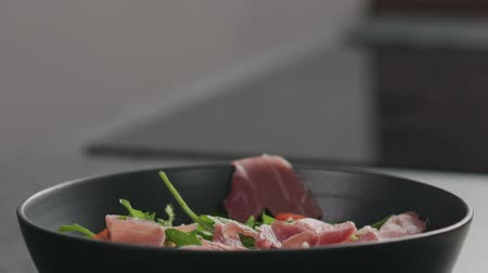 aggiungi : Slow motion prosciutto falling to make salad with arugula, and tomatoes