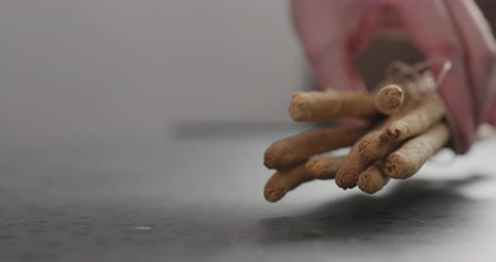 grissini : Slow motion man hand put bunch of homemade grissini on concrete countertop