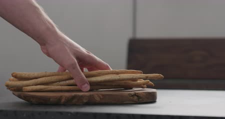 bread stick : Slow motion man hand put bunch of homemade grissini on olive board