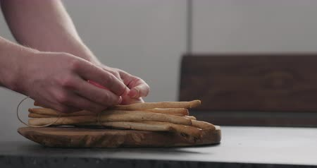 grissini : Slow motion man hand tying bunch of homemade grissini on olive board Stock Footage