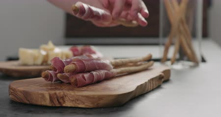 grissini : Slow motion man hand take grissini with prosciutto from olive board