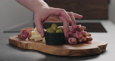 antipasti : Slow motion man hand put olives on olive board next to grissini with prosciutto and parmesan pieces Stock Footage