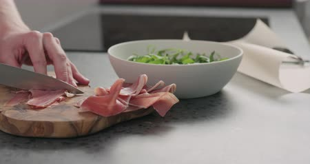 spek : Slow motion man cut prosciutto on olive board Stockvideo