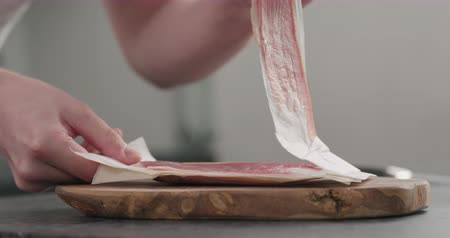 spek : Slow motion man unpack prosciutto on olive board Stockvideo