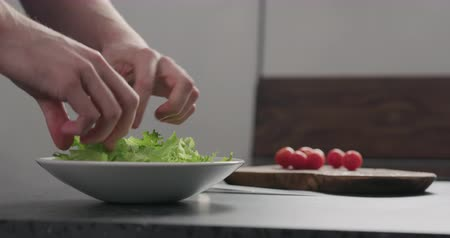 eklemek : Slow motion add frisee salad leaves into white bowl
