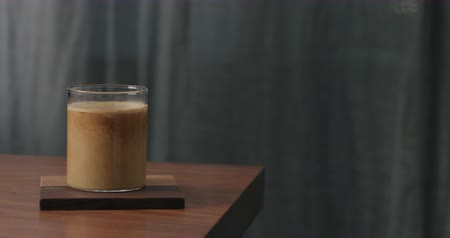 poured out : Slow motion cream pour into coffee in glass on walnut table Stock Footage