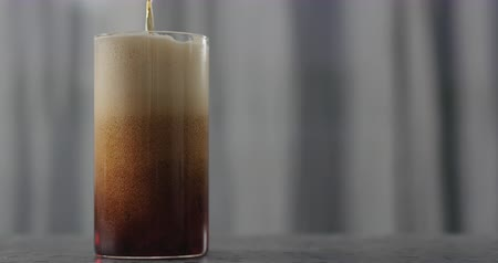 craft beer : Slow motion dark beer pour into glass on concrete countertop