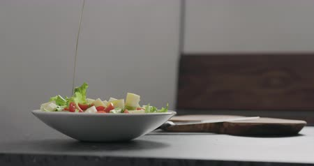 девственница : Slow motion adding olive oil to make salad in white bowl Стоковые видеозаписи