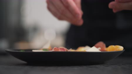 spek : making salad man adding parmesan into black plate with arugula, prosciutto and tangerine Stockvideo