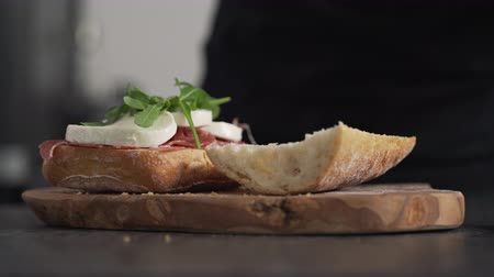šunka : man add arugula on ciabatta on olive board