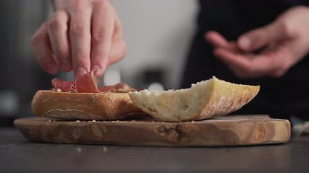 incir : man add prosciutto on ciabatta on olive board