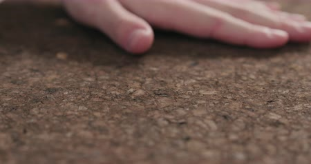 cartelloni : Slow motion man hands touch dark cork surface Filmati Stock