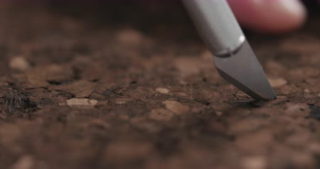 cork board : Slow motion man snijden donkere cork met hobby mes close-up