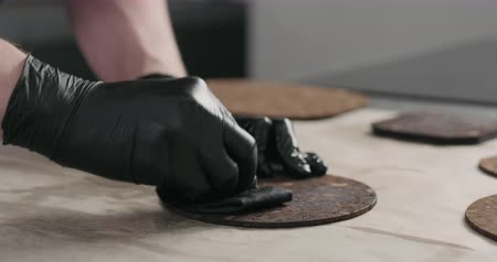 queimado : Slow motion man hands applying oil finish on dark cork coaster Vídeos