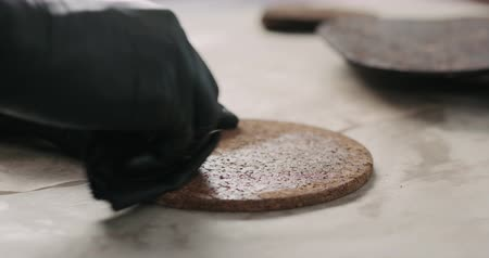 acabamento : Slow motion man hands applying oil finish on cork coaster
