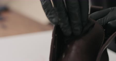 sapato : Slow motion man hands in black gloves applying protective cream to brown leather chukka boots