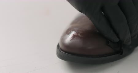 buty : Slow motion man hands in black gloves applying protective cream to brown leather chukka boots