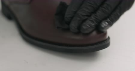 szewc : Slow motion man hands in black gloves applying protective cream to brown leather chukka boots