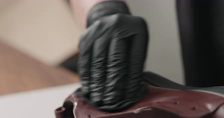buty : Slow motion man hands in black gloves applying protective cream to brown leather sneakers