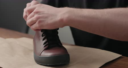 szewc : Slow motion remove laces from sneakers before maintenance Wideo
