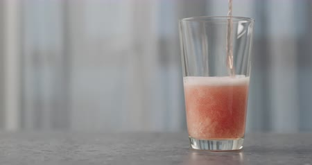občerstvení : Slow motion pour orange fizzy drink into pint glass on concrete countertop with copy space