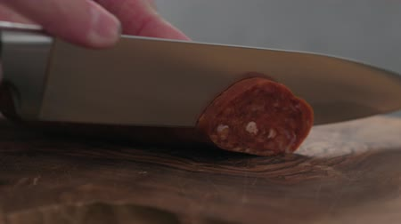 fumado : Slow motion slicing chorizo sausage on olive wood board closeup