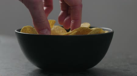 Slow motion man hand take round corn chips from black bowl closeup