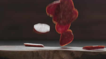 kiełbasa : Slow motion chorizo slices falls onto olive wood board closeup