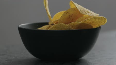 mexicano : Slow motion round corn chips falling into black bowl closeup