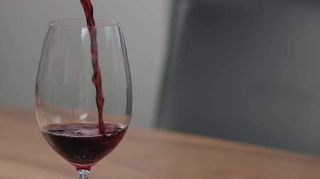 orzech : Slow motion pour red wine into wineglass on walnut table with copy space