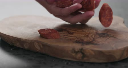 kiełbasa : Slow motion man put chorizo slices on olive wood board closeup