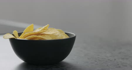 fried : Slow motion round corn chips falling into black bowl closeup