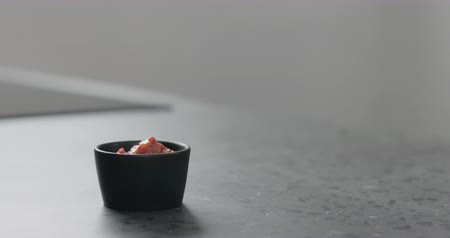 Slow motion put salsa in small black bowl on concrete surface Stock Footage