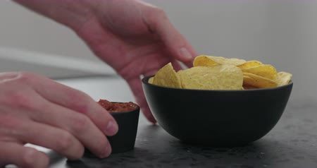 dips : Slow motion man hands serve corn chips with salsa on concrete surface