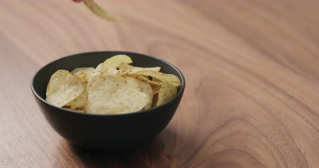 batatas : Slow motion man hand take potato chip with black pepper from black bowl on walnut table