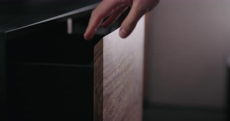 Slow motion man hand open and close tv stand drawer closeup Wideo