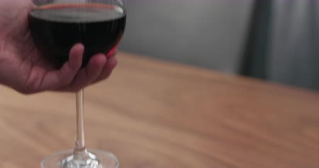 Slow motion man hand take wineglass with red wine from walnut table with copy space