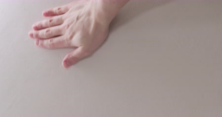 Slow motion man hand touching white wall