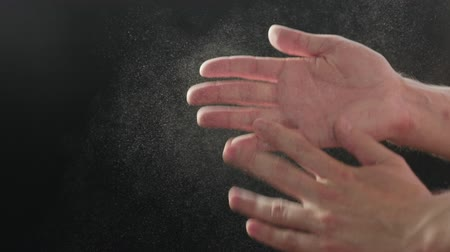 Slow motion closeup man clapping hands with fine powder