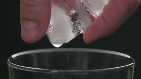 občerstvení : Slow motion man add ice cubes into glass on black background closeup