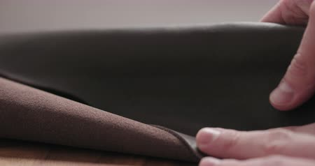 Slow motion man hand checking brown leather piece closeup Wideo