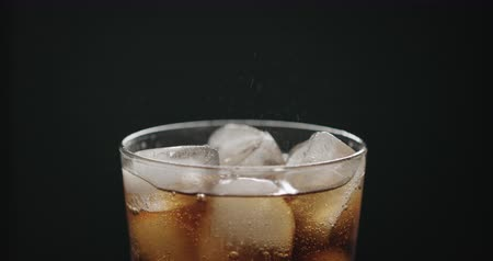 Slow motion cola in glass with ice cubes on black background closeup Stock Footage